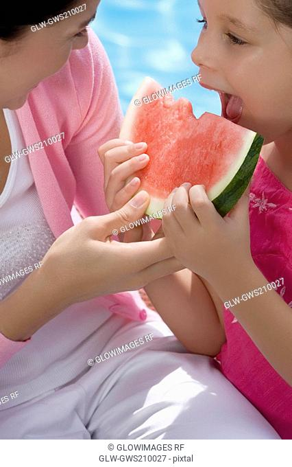 Close-up of a girl eating a slice of watermelon