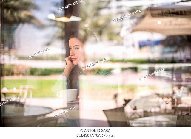 Woman gazing behind reflective cafe window, Dubai, United Arab Emirates