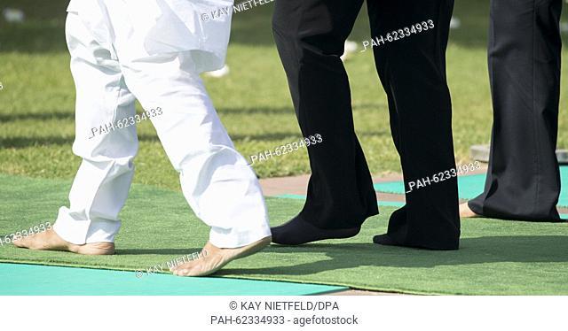 German Chancellor Angela Merkel (black pants) walks on socks the memorial to independence hero Mahatma Gandhi in New Dehli, India, 05 October 2015