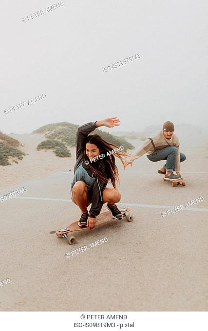 Young couple skateboarding in misty beach carpark, Jalama, California, USA