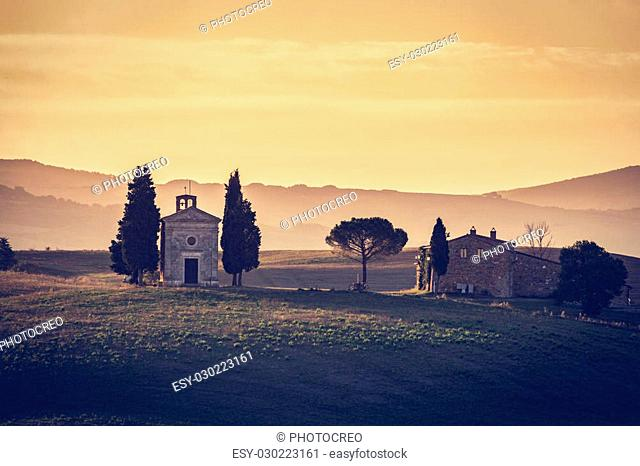 Tuscany landscape at sunrise with a chapel of Madonna di Vitaleta, San Quirico d'Orcia, Italy. Vintage