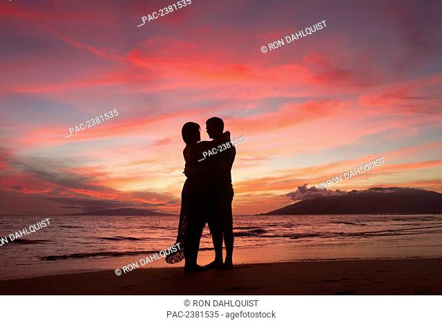 Silhouette of a couple on their honeymoon standing on Keawekapu Beach at sunset; Wailea, Maui, Hawaii, United States of America