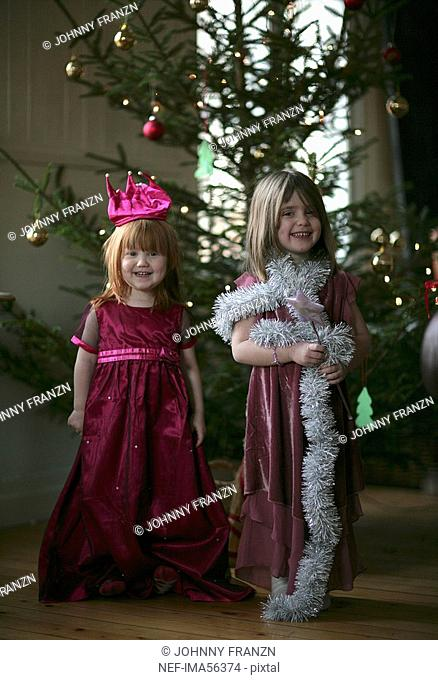 Two girls in dresses in front of a Christmas tree Sweden