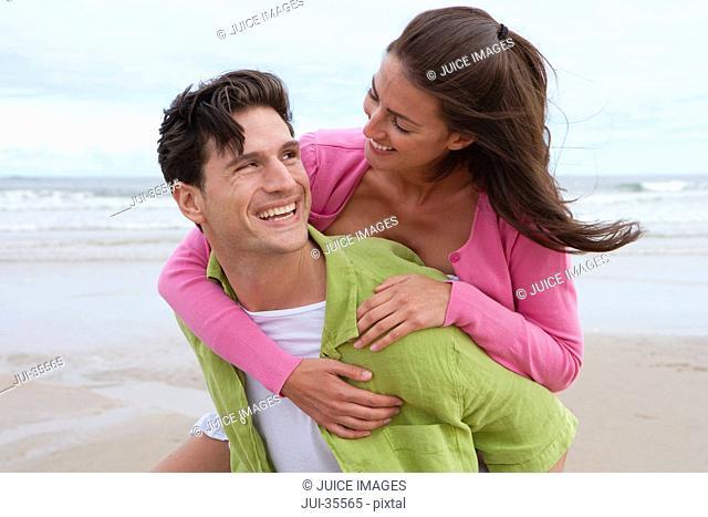 Man Giving Woman Piggyback Along Summer Beach