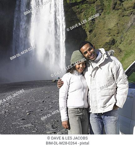Couple in winter clothes hugging in front of waterfall