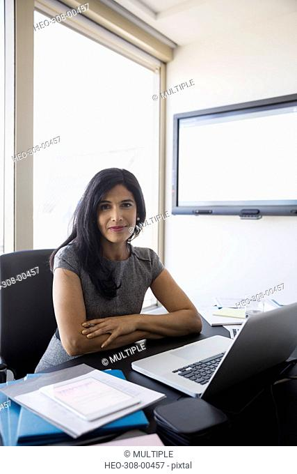Portrait confident businesswoman working at laptop in conference room