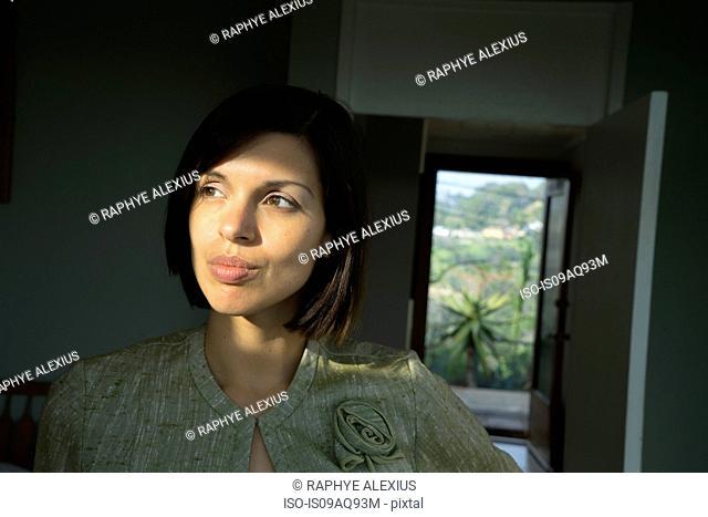 Portrait of beautiful sunlit mid adult woman in hallway