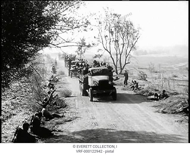 Roadside soldiers waving to passing military trucks