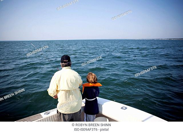 Boy and grandfather fishing from boat, Falmouth, Massachusetts, USA