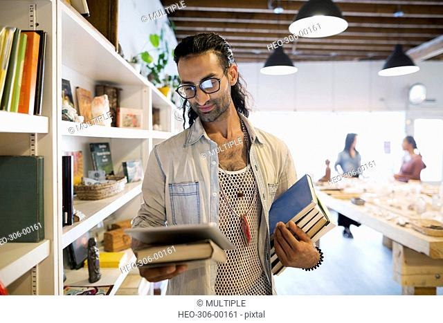 Male shop owner with digital tablet and books