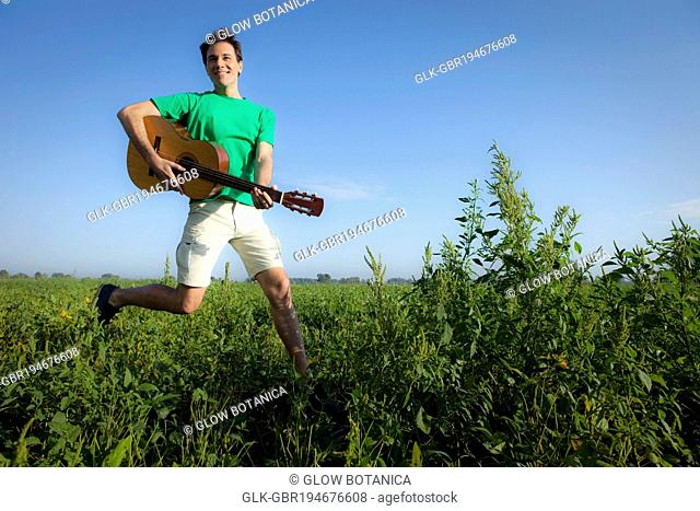 Man holding a guitar and jumping in a field