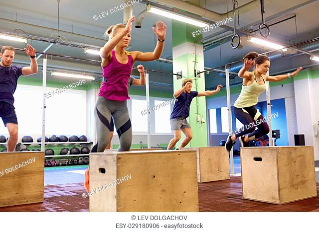 fitness, sport, training and exercising concept - group of people doing box jumps in gym (motion blurred image)