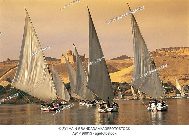 Feluccas on the Nile, Aga Khan mausoleum in background. Aswan. Egypt
