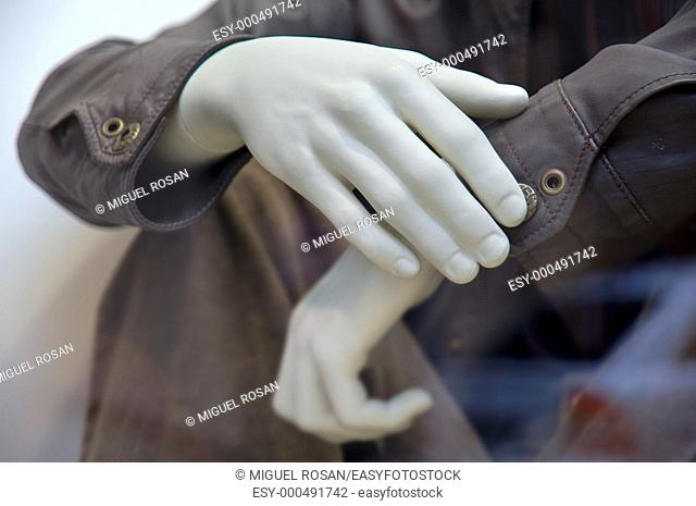 Male hands folded in plastic showcase a fashion store