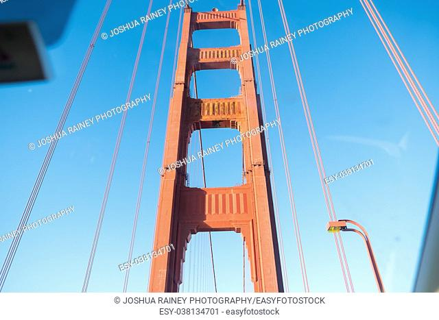 Golden Gate Bridge tower support shot through a vehicle windshield while driving