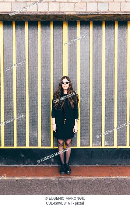 Portrait of young woman, in urban environment