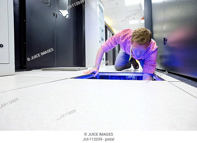 Technician checking cabling under floor of data centre server room