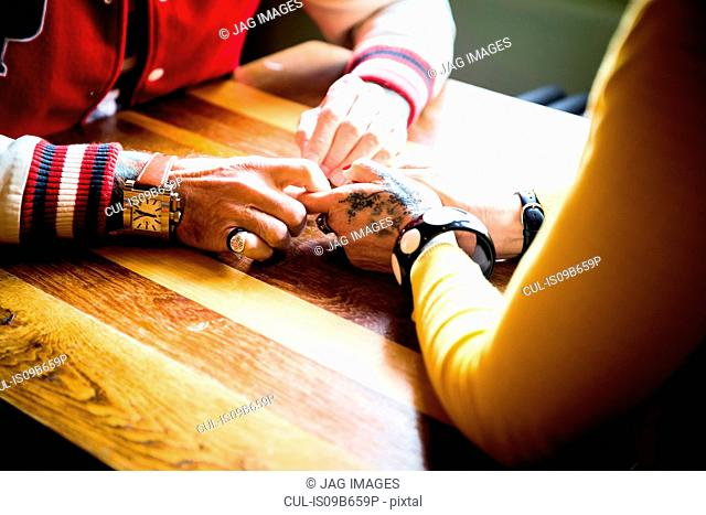 Couple holding hands on table