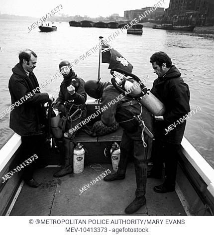 Members of the Underwater Search Unit of the Metropolitan Police preparing for a dive in the River Thames, London, from a Thames Division launch