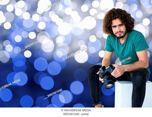 3d photographer with camera on the hands, sitting. Blue bokeh background