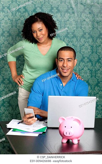 Couple paying bills by using online banking at home