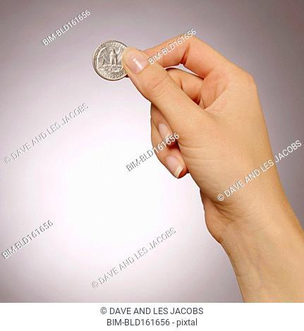 Caucasian woman holding quarter coin