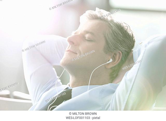 Relaxed businessman with earbuds