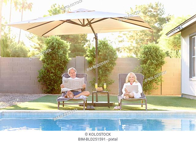 Caucasian couple reading newspaper and using laptop near swimming pool