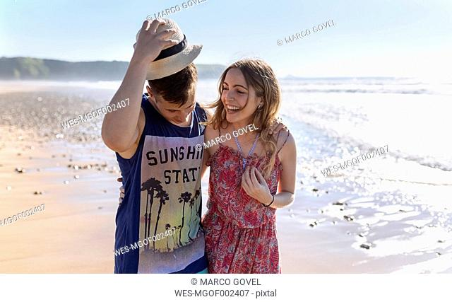 Happy young couple in love walking along the beach