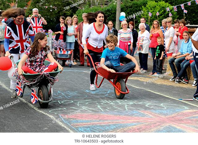 People Celebrating The Queen's Diamond Jubilee Taking Part In A Wheelbarrow Race With Crowds Watching At A Street Party Surrey England