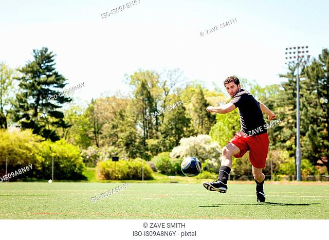 Soccer player running and kicking ball
