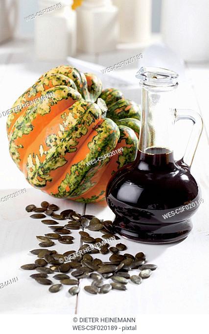Multicoloured squash (Cucurbita maxima), pumpkin seeds and carafe with pumpkin seed oil, studio shot