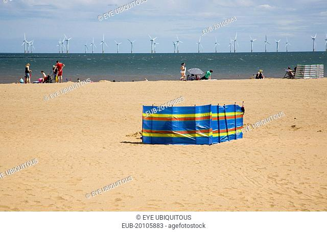 Wind Farm offshore on the horizon with families and windbreaks on the beach