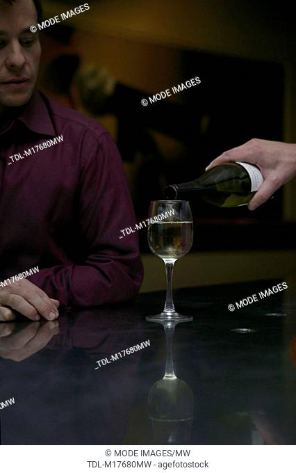 A bartender pouring a glass of white wine, cropped