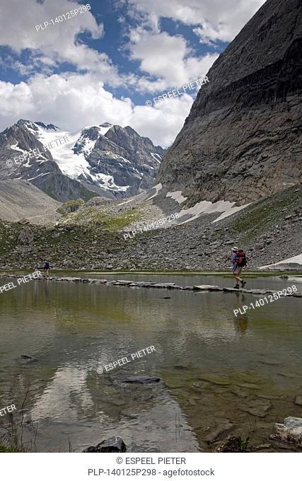 Mountain walkers crossing the alpine lake Lac des Vaches in the Parc National de la Vanoise, France