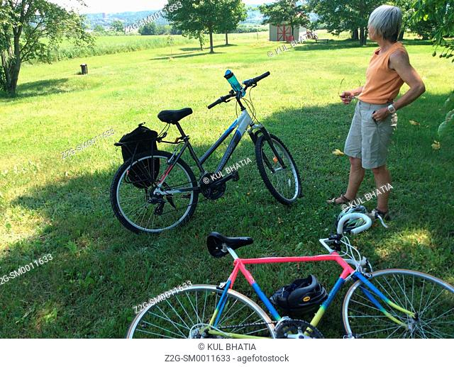 A woman cyclist takes a break in the lush Annapolis Valley, Nova Scotia, Canada