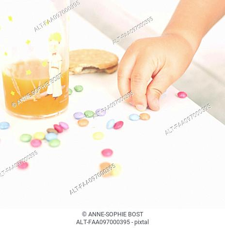 Child picking up candies from table