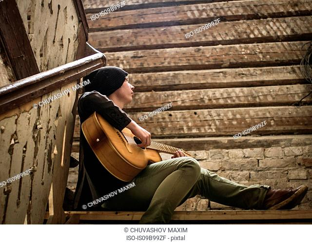Young man sitting on stairs, playing guitar
