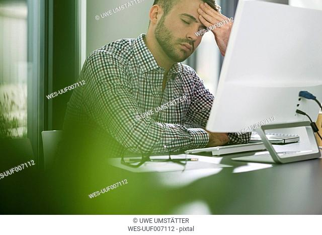 Tired young man at desk in office