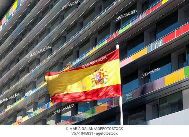 Spanish flag waving and INE building, Paseo de la Castellana. Madrid, Spain
