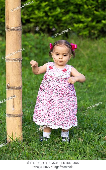 Baby Girl playing in the grass nextto a bambu