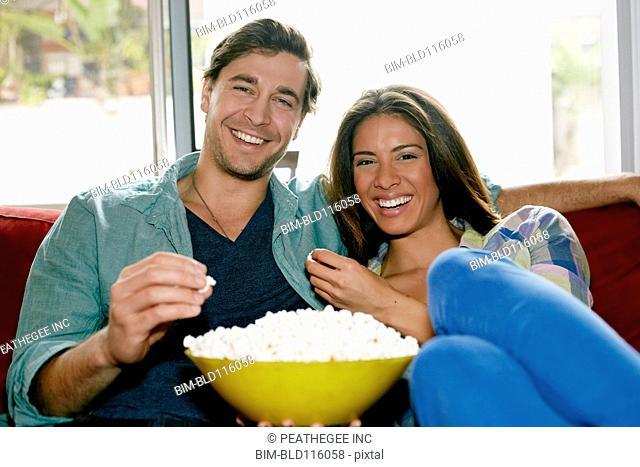 Couple eating popcorn on sofa