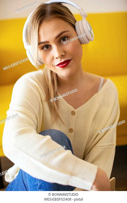 Blonde woman with headphones using smartphone at home