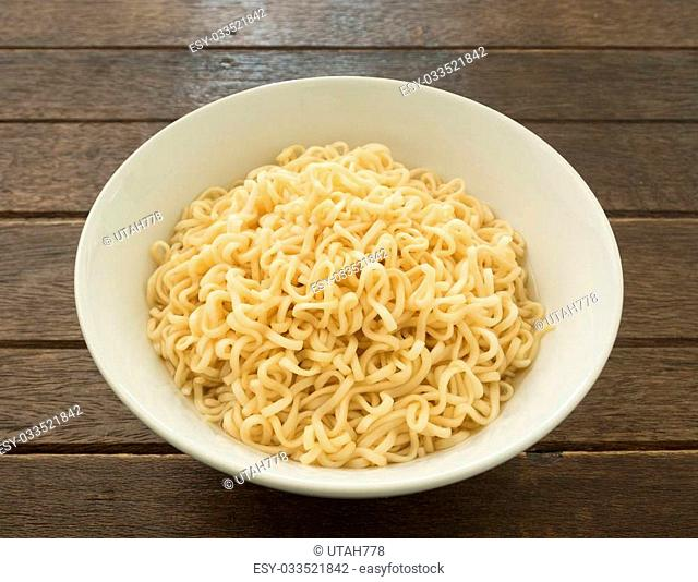 Instant noodles in bowls on wood table