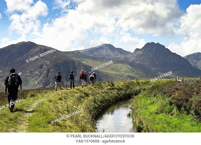 Ogwen, Conwy  North Wales, UK, Europe  Ramblers group walking along a watercourse with view along the Ogwen valley to Tryfan and the Glyders in Snowdonia...