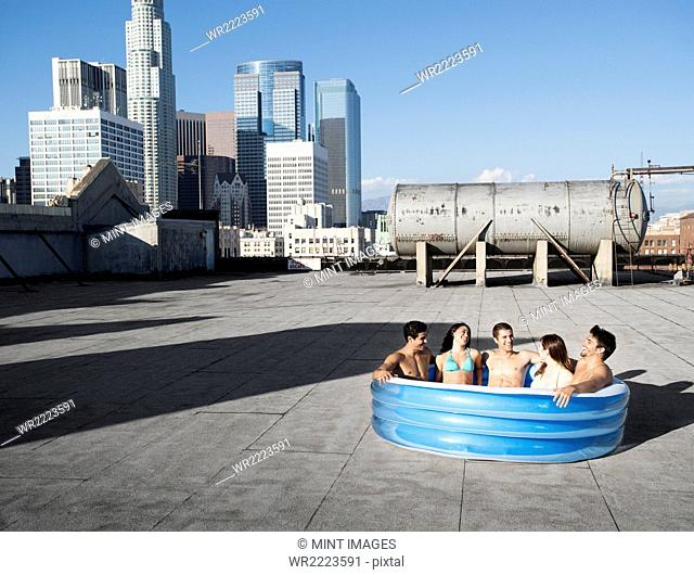 A group of friends, men and women sitting in a small inflatable water pool on a city rooftop, cooling down