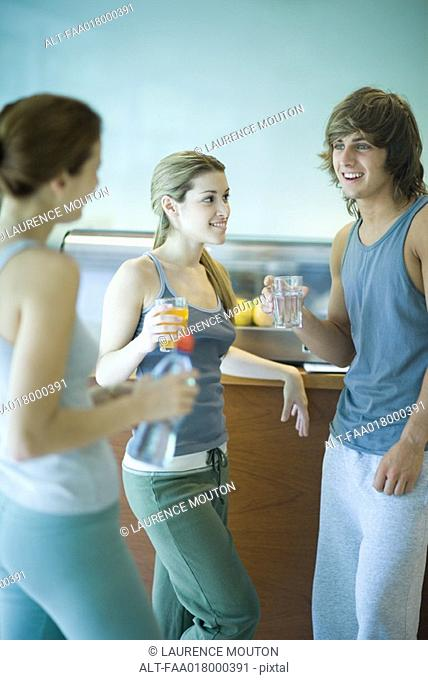 Young adults wearing exercise clothes, standing in cafeteria, having healthy snack and chatting