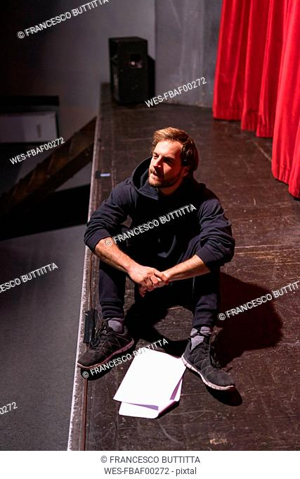 Rehearsing actor sitting on stage of theatre with script