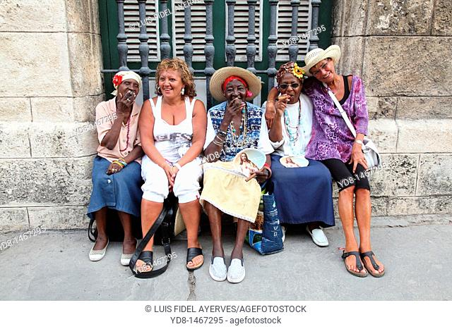 Brunettes women smoking cigars black woman representative to the Cuban typical of the time with two tourists in Old Havana, Cuba