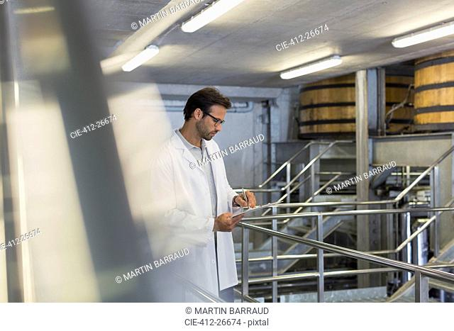 Vintner in lab coat with clipboard in winery cellar